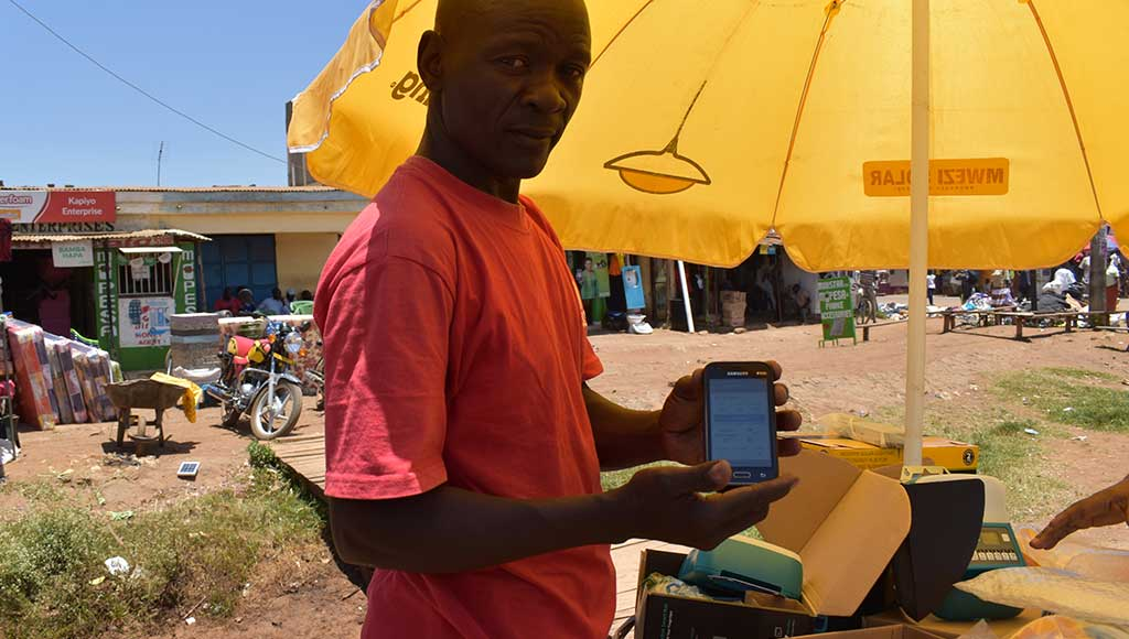 Mwezi sales agent Morris uses the Angaza Activator app to make new sales and track payments